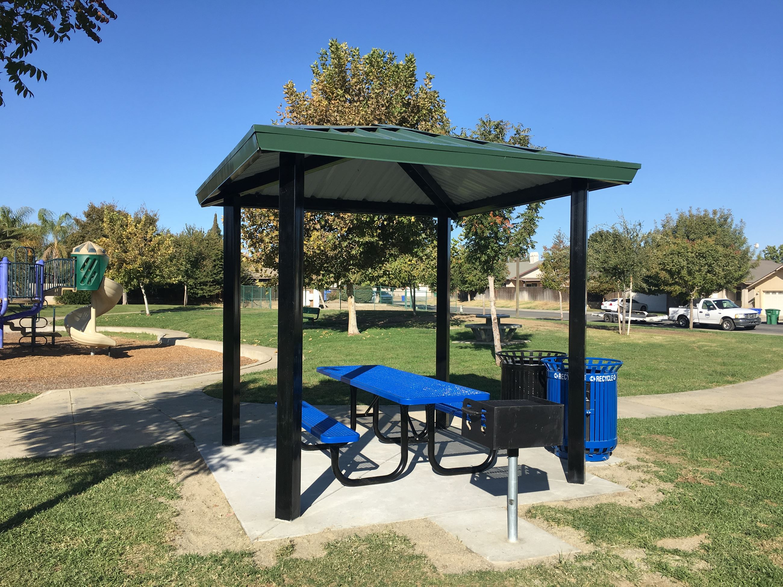 Sandalwood Park Awning  shade structure with 8ft table,bbq pit, and trash cans.